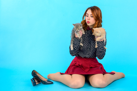 Photo for young girl with long hair and in fashionable clothes sits on a blue background and holds two cats, next to her are her black shoes - Royalty Free Image