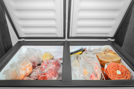 Foto de Frozen food in the freezer. Bagged frozen meat and other foods in a horizontal freezer with the two doors open. Food preservation. - Imagen libre de derechos