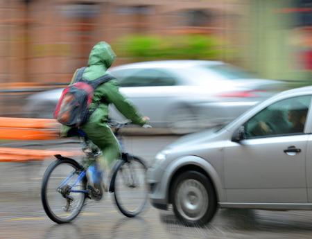 Foto de Dangerous city traffic situation with cyclist and  car in the city in motion blur - Imagen libre de derechos