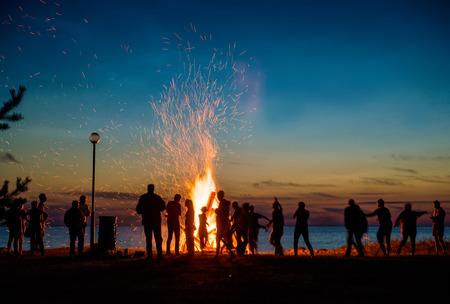 Photo pour People resting near big bonfire outdoor at night - image libre de droit