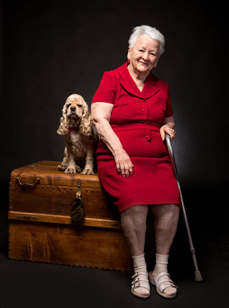 Photo pour Old woman with american spaniel on a dark background - image libre de droit