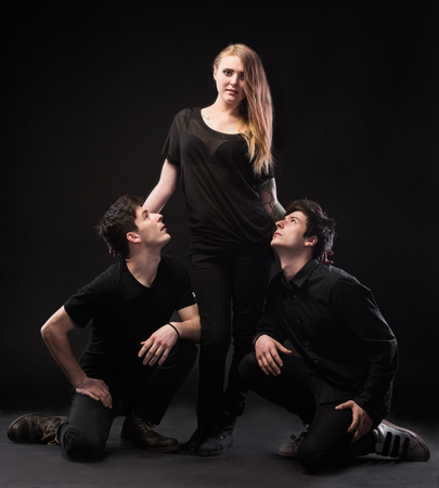 Photo pour One woman and two men on a black background - image libre de droit