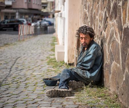 Foto de Homeless man on the street of the city. Senior beggar - Imagen libre de derechos