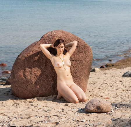 Photo for Young nude woman lying on stone against the sea background. Enjoying sunny day and summer time - Royalty Free Image