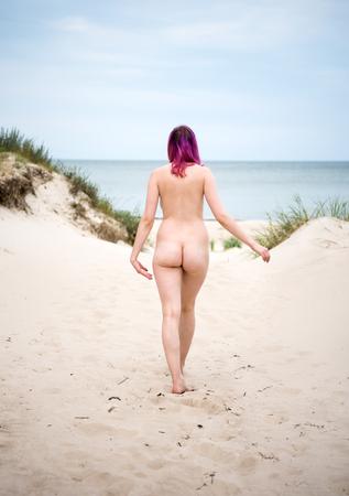Foto de Young nude woman posing on a sandy beach. Sexy female enjoying hot summer day outdoors - Imagen libre de derechos