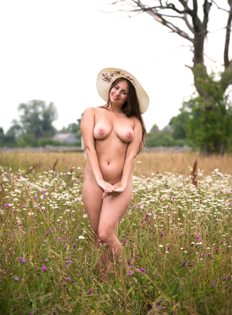 Photo for Romantic image of young naked woman in white hat  posing outdoors. Sexy brunette enjoying summer time in hot day - Royalty Free Image