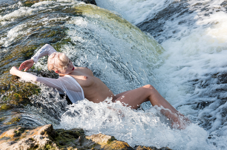 Photo for Beautiful young seminude woman in white shirt enjoying summertime in the waterfall. Enjoying and relaxing in the water.Sexy blonde outdoors - Royalty Free Image