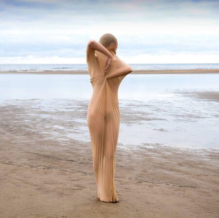 Foto de Nude model posing in stocking in the sea at the beach. Sexy woman outdoors - Imagen libre de derechos