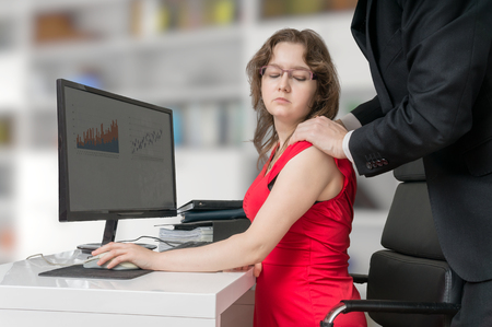 Photo pour Harassment at workplace. Boss or manager is touching shoulder of his secretary in office. - image libre de droit