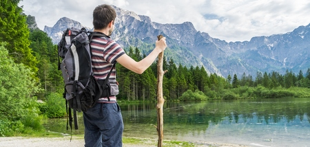 Photo for Hiking tourist from behind and lake near Alps in Almsee in Austria. Panoramic photo. - Royalty Free Image