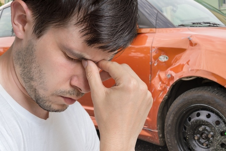 Photo for Young sad man had car accident. Damaged car in background. - Royalty Free Image