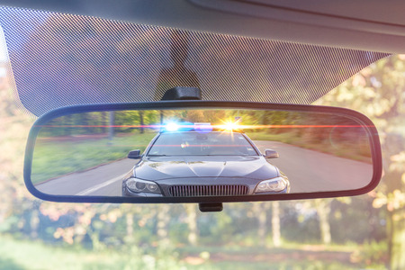 Photo pour View on rear mirror of a car. Police car with lights and siren is chasing you. - image libre de droit