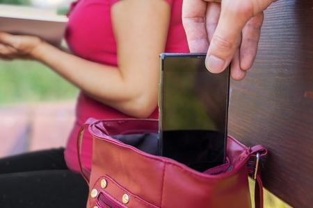 Foto de Pickpocket thief is stealing smartphone from bag of a woman reading book. - Imagen libre de derechos
