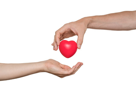 Foto de Heart transplant and organ donation concept. Hand is giving red heart. Isolated on white background. - Imagen libre de derechos