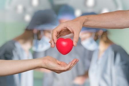 Foto de Organ donation concept. Hand is giving heart. Surgeons in background. - Imagen libre de derechos