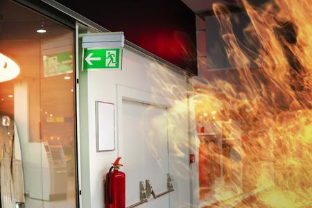 Foto de Emergency fire exit sign and fire in shopping mall. - Imagen libre de derechos