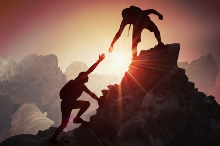 Photo for Help and assistance concept. Silhouettes of two people climbing on mountain and helping. - Royalty Free Image
