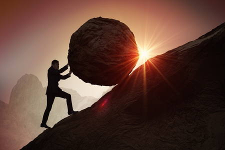 Photo pour Sisyphus metaphore. Silhouette of businessman pushing heavy stone boulder up on hill. - image libre de droit