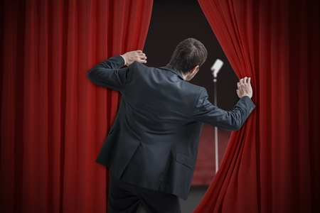 Photo for Nervous man is afraid of public speech and is hiding behind curtain. - Royalty Free Image