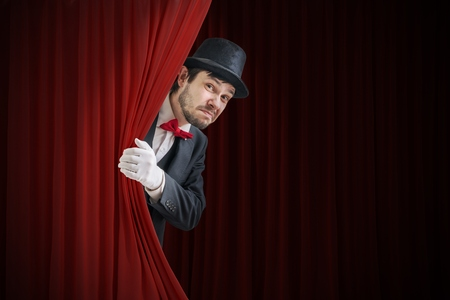 Photo for Nervous actor or illusionist is hiding behind red curtain in theater. - Royalty Free Image
