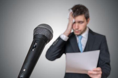 Photo for Nervous man is afraid of public speech and sweating. Microphone in front. - Royalty Free Image