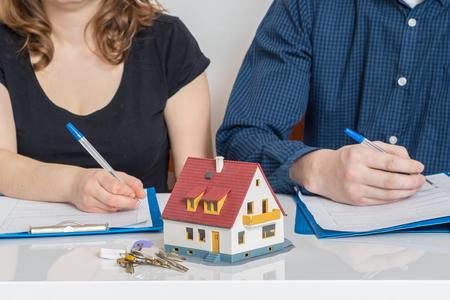 Photo pour Divorce and dividing a property concept. Man and woman are signing divorce agreement. - image libre de droit