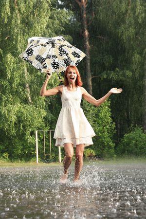 happy young woman running under rain
