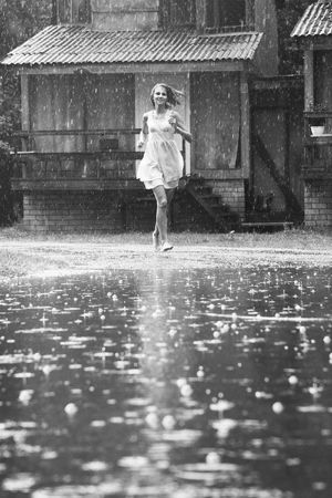 young woman running in the rain without umbrella