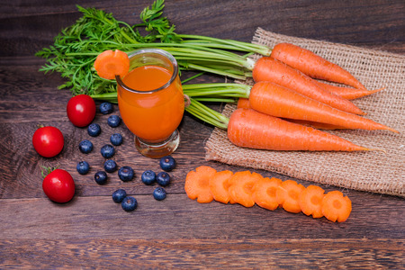 Photo pour Healthy eating and dieting concept,fresh carrot  and carrot juice or organic healthy juice in glass , tomato ,fruit,vegetables on a grey wooden table wall background with copy space . - image libre de droit