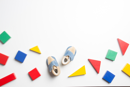Foto de Colorful wooden blocks and baby shoes on white background - Imagen libre de derechos