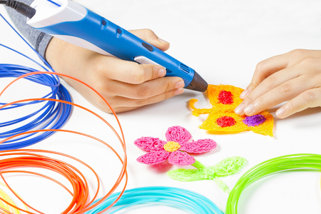 Photo pour Kid hand holding blue 3d printing pen and making new item - image libre de droit