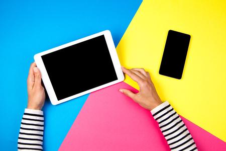 Foto de Womans hands with tablet computer and smartphone on colorful background. - Imagen libre de derechos