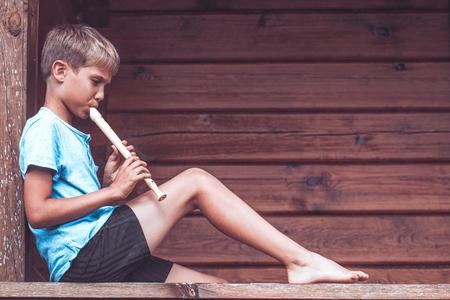 Photo pour Boy sitting on terrace and playing flute outdoors - image libre de droit