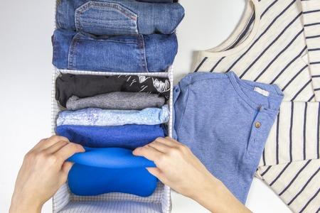 Foto de Woman hands tidying up kids clothes in basket. Vertical storage of clothing, tidying up, room cleaning concept - Imagen libre de derechos