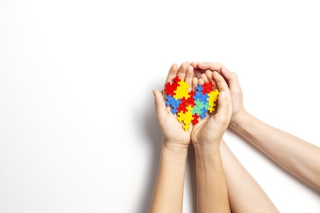 Foto de Hands holding colorful heart on white background. World autism awareness day concept - Imagen libre de derechos