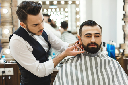 Photo pour Handsome dark haired man wearing white shirt making beard form with scissors for man with black hair at barber shop, mirror at background. - image libre de droit