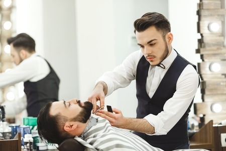Photo pour A man with dark hair wearing white shirt making beard form with scissors for man with black hair at barber shop, mirror at background, portrait. - image libre de droit