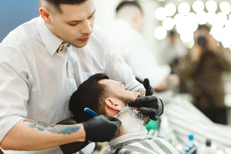 Photo pour Handsome Dark haired man with tattoo wearing white shirt and gloves making beard form with razor for man with black hair at barber shop, portrait. - image libre de droit