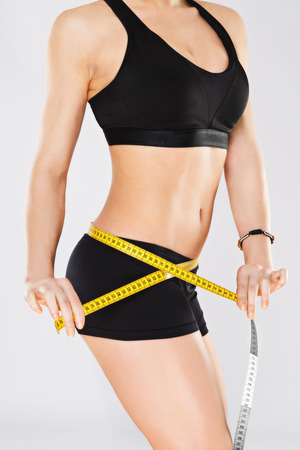 Foto de Holding yellow measuring tape on waist - Imagen libre de derechos