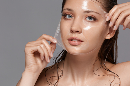 Foto de beautiful woman removing peeling mask from her face and looking to the camera, copy space, moisturizing effect - Imagen libre de derechos