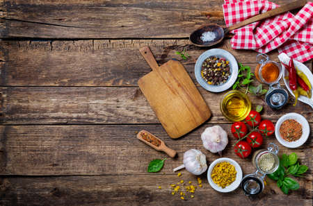 Foto de Ingredients for cooking and empty cutting board on an old wooden table. Food background  with copyspace - Imagen libre de derechos