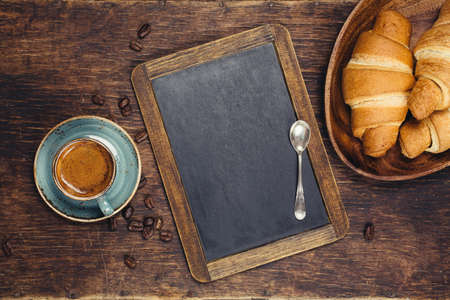 Foto de Croissants and coffee with blackboard. Food background concept with copyspace - Imagen libre de derechos