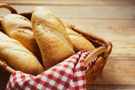 Foto de Fresh bread in  basket on a wooden table - Imagen libre de derechos