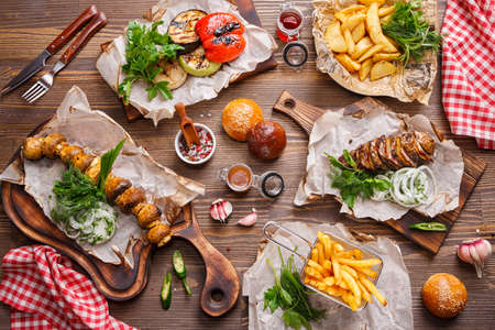 Photo pour Different food on a wooden table. Grilled vegetables, baked potatoes, French fries and Grilled mushrooms. Food background, Top view - image libre de droit