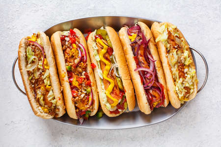 Foto de Hot dogs fully loaded with assorted toppings on a tray. Top view - Imagen libre de derechos