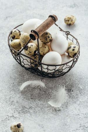 Foto de Fresh farm Quail and chicken eggs in a basket. - Imagen libre de derechos