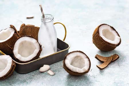 Foto de Refreshing coconut water in a small bottle and coconuts on a blue - Imagen libre de derechos