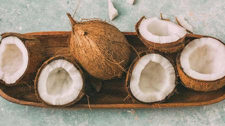 Foto de Fresh coconuts with coconut halves on a tray, close-up, top view. - Imagen libre de derechos