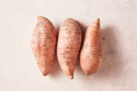 Photo for Three large sweet potatoes on a textured pink background, top view. - Royalty Free Image
