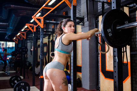 Photo for Crossfit and sport theme. beautiful sexy girl with bare booty in a bikini and Tshirt stands tired near the bar and rests after training with heavy weight. Deadlift and training of leg and back muscles - Royalty Free Image